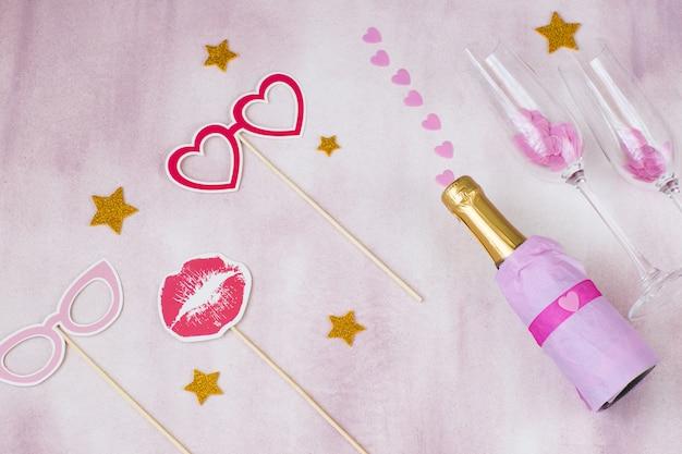 Op een roze achtergrond, een fles champagne, feeststickers en roze harten - vrijgezellenfeest