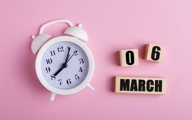 Op een roze achtergrond, een witte wekker en houten blokjes met de datum van 06 maart