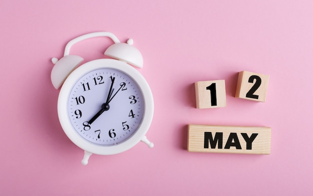 Op een roze achtergrond, een witte wekker en houten blokjes met de datum van 12 mei