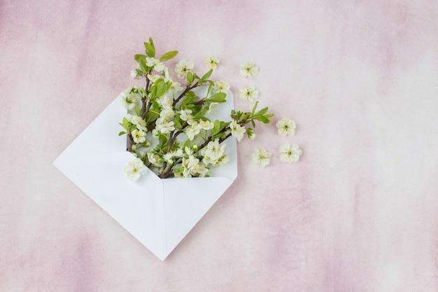 Op een roze achtergrond in een envelop van kersentakken