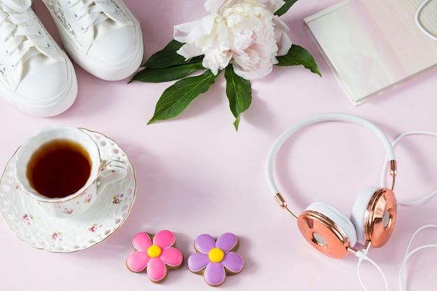 Op een roze achtergrond: koptelefoons, sneakers, pioenroos, een kopje thee