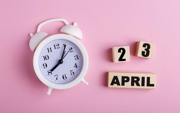 Op een roze ondergrond, een witte wekker en houten blokjes met de datum van 23 april.