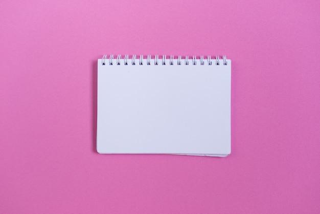 Op een roze oppervlak staat een wit notitieboekje