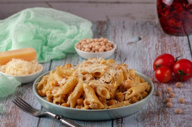 Op een schotel italiaanse deegwaren met kikkererwten, kruiden en tomaten - close-up