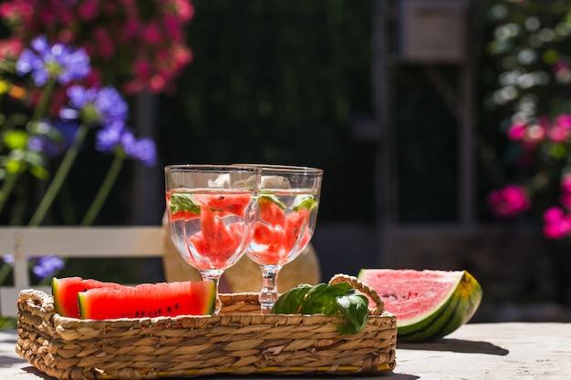 Op een tafel in de tuin in een mand staan twee glazen limonade en in plakjes gesneden watermeloen