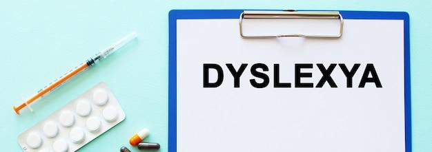 Op een tafel ligt een klembord met papier. inschrijving dyslexya. medisch concept.