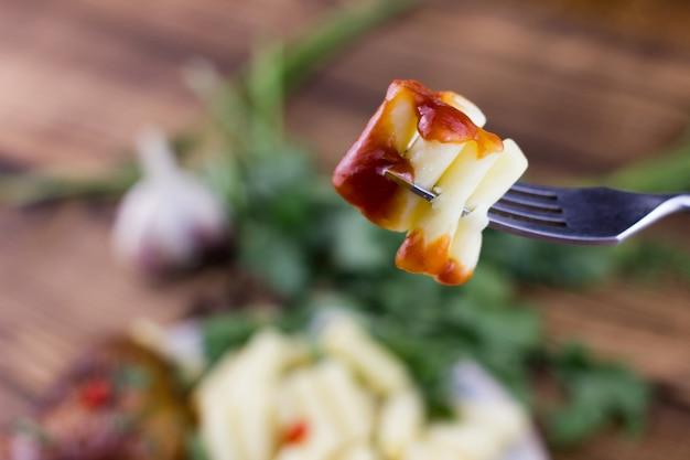 Op een vork pasta met ketchup, gekookte italiaanse pasta op een vork close-up