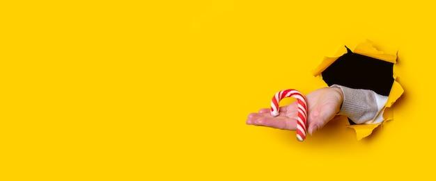 Op een vrouwelijke palm houdt een kerstsnoep op een gescheurde gele achtergrond. banier.