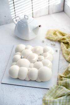 Op een wit bord, een theepot en een mousse cake met aardbeienvulling met een fluwelen witte coating in de vorm van bubbels