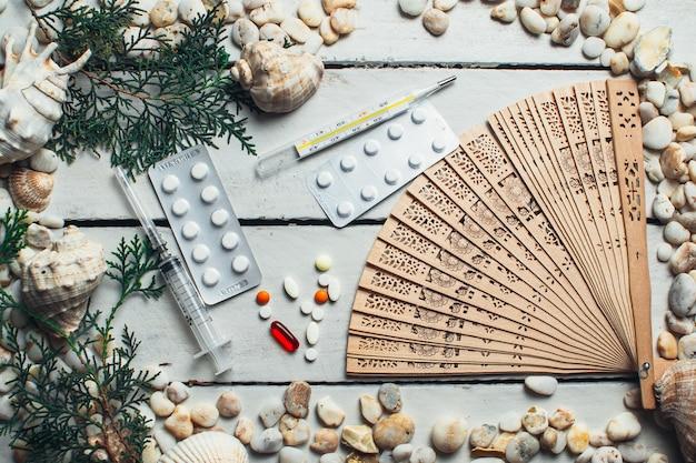 Op een wit houten oppervlak liggen de schelpen en medische hulpmiddelen