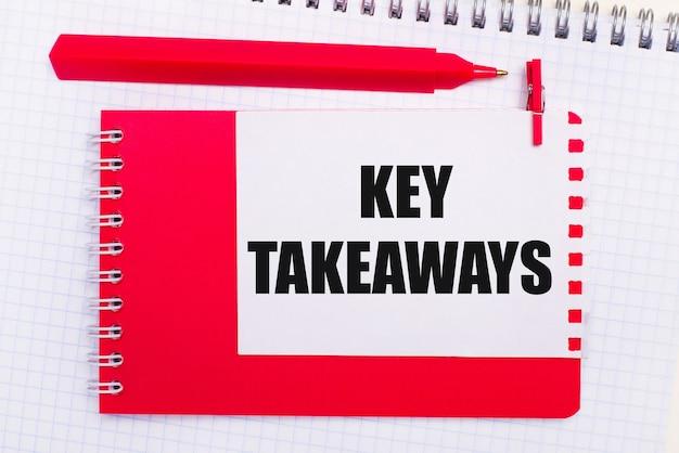Op een wit notitieblok, een rode pen, een rood notitieblok en een wit vel papier met de tekst key takeaways