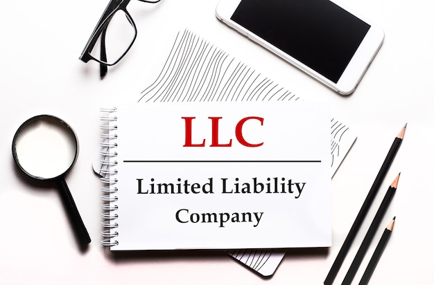 Op een witte achtergrond een bril, een vergrootglas, potloden, een smartphone en een notitieboekje met de tekst llc limited liability company