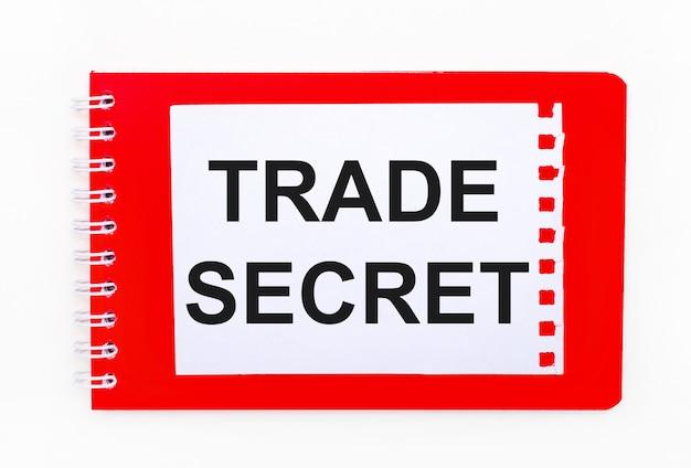 Op een witte achtergrond - een helder rood notitieboekje op een spiraal. daarop ligt een wit vel papier met de tekst trade secret