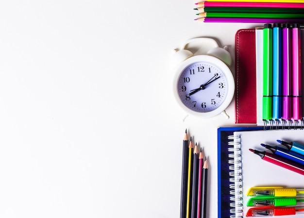Op een witte achtergrond liggen veelkleurige potloden, stiften, viltstiften en een witte wekker. kopieer ruimte