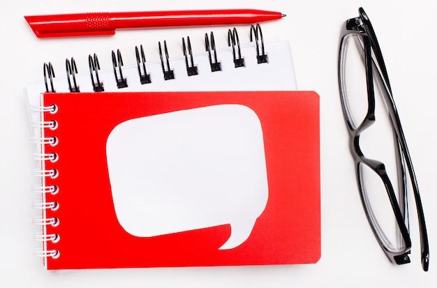 Op een witte achtergrond, witte en rode blocnotes, zwarte glazen, een rode pen en een witte lege kaart met een plaats om tekst in te voegen.