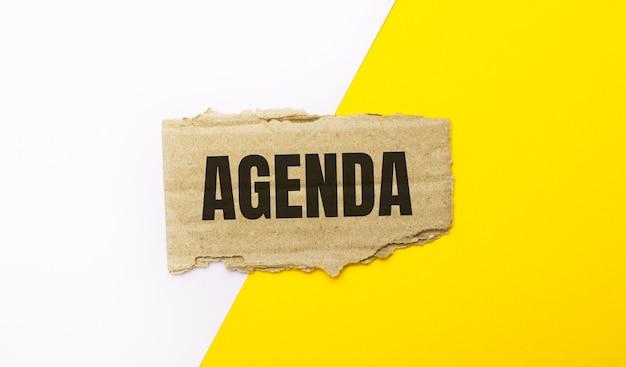Op een witte en gele ondergrond, bruin gescheurd karton met de tekst agenda