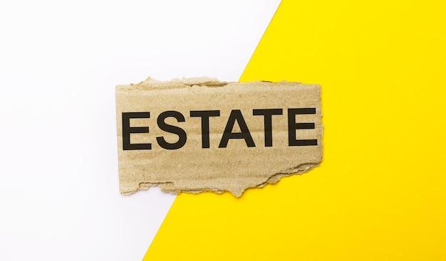 Op een witte en gele ondergrond, bruin gescheurd karton met de tekst estate