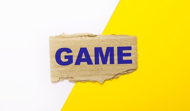 Op een witte en gele ondergrond, bruin gescheurd karton met de tekst game