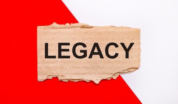 Op een witte en rode ondergrond, bruin gescheurd karton met de tekst legacy