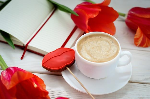 Op een witte houten tafel staat een rood notitieboek met tulpen, er staat een kopje koffie en peperkoek in de vorm van rode lippen