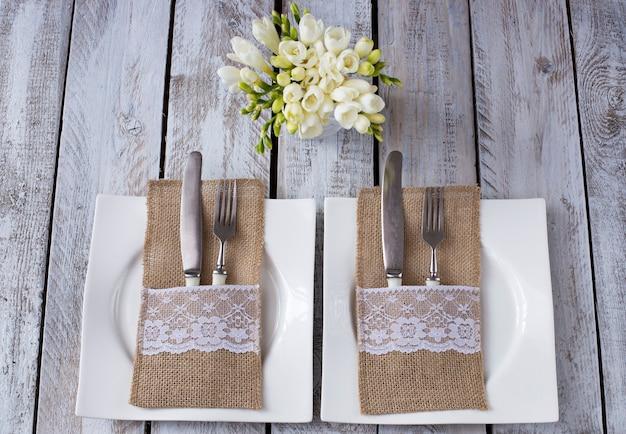 Op een witte houten tafel, twee borden, vorken en messen, bloemen in een vaas - een feestelijke achtergrond (verjaardag, bruiloft, 8 maart, romantisch diner)