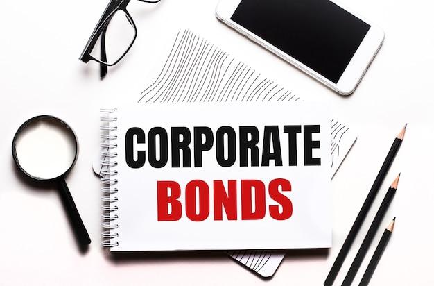Op een witte muur bril, vergrootglas, potloden, smartphone en notitieboekje met de tekst corporate bonds