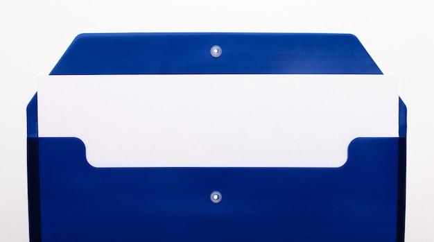 Op een witte muur, een blauwe map voor papieren met een leeg vel papier. kopieer ruimte.