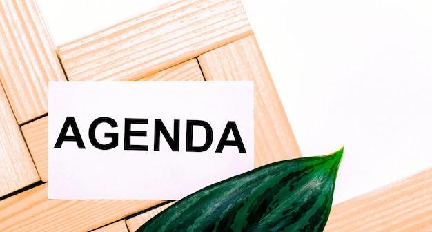 Op een witte ondergrond houten bouwblokken, een witte kaart met de tekst agenda en een groen blad van de plant. uitzicht van boven.