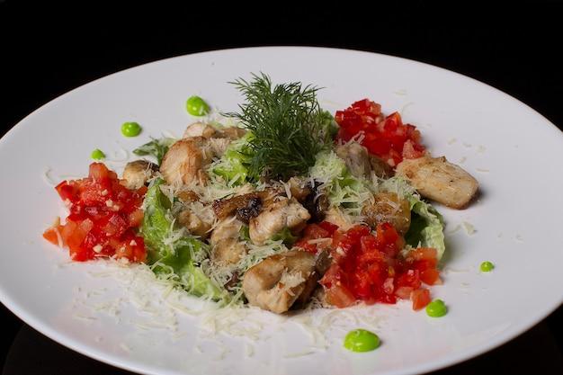 Op een witte plaat salade van vlees, tomaten, sla, dille, bestrooid met kaas, op een zwarte achtergrond. gebakken vlees met groenten.