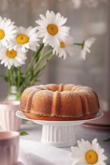 Op een witte schaal een ronde cupcake, rond met een gaatje, bestrooid met poedersuiker