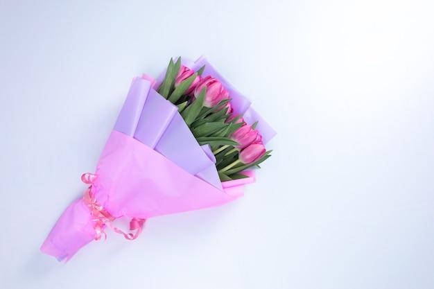 Op een witte tafel ligt een boeket feestelijke lentetulpen verpakt in een roze wikkel