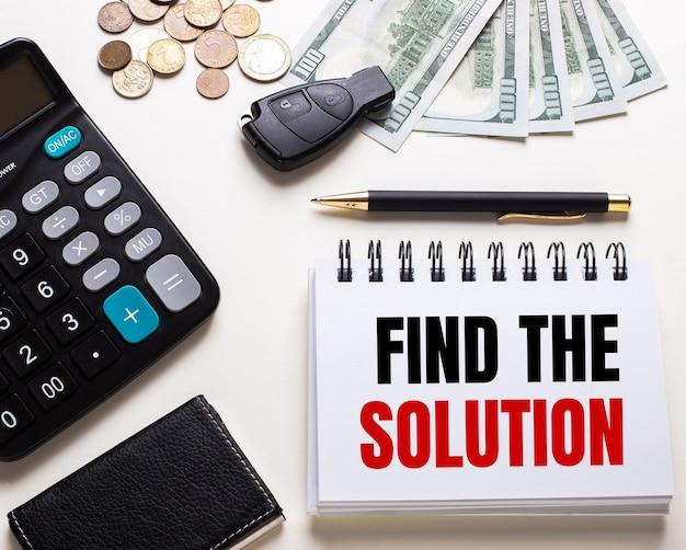 Op een witte tafel staat een rekenmachine, een autosleutel, contant geld, een pen en een notitieboekje met het opschrift vind de oplossing