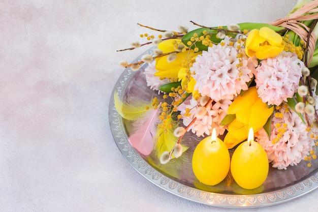 Op een zilveren dienblad een boeket hyacinten en tulpen, twee kaarsen in de vorm van eieren, veren