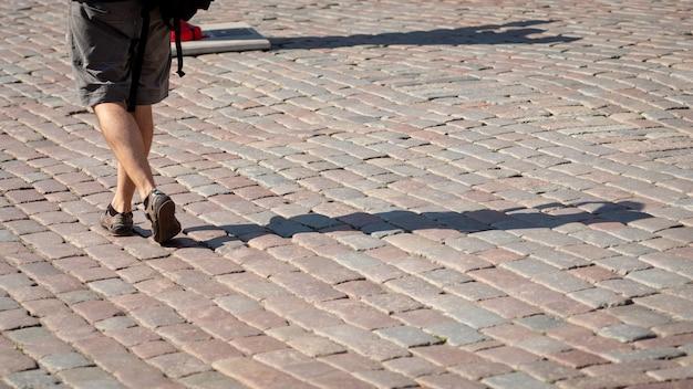 Op een zonnige dag loopt een man over het trottoir. de menselijke schaduwen zijn zichtbaar op het trottoir. uitzicht vanaf de achterkant.