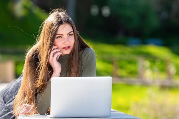 Op een zonnige en winderige dag jonge lachende vrouw liggend op een bankje in het park en die op laptop werkt en praten over een smartphone