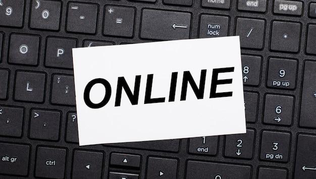 Op een zwart computertoetsenbord zit een witte kaart met de tekst online.