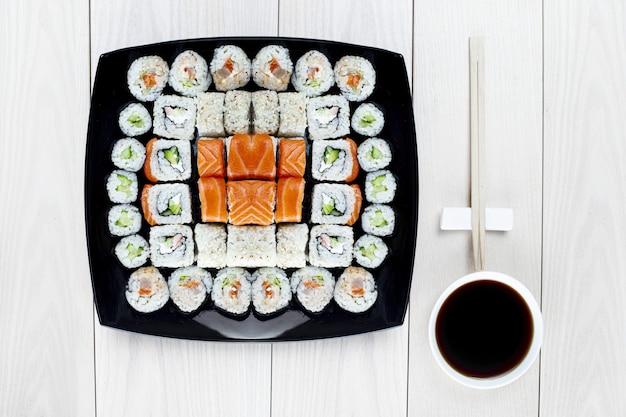 Op een zwart vierkant bord wordt een grote sushi-set neergelegd. bovenaanzicht. lichte houten tafel. ernaast staat een kom sojasaus en een eetstokje. heerlijke lunch of diner in japanse stijl. zachte focus.