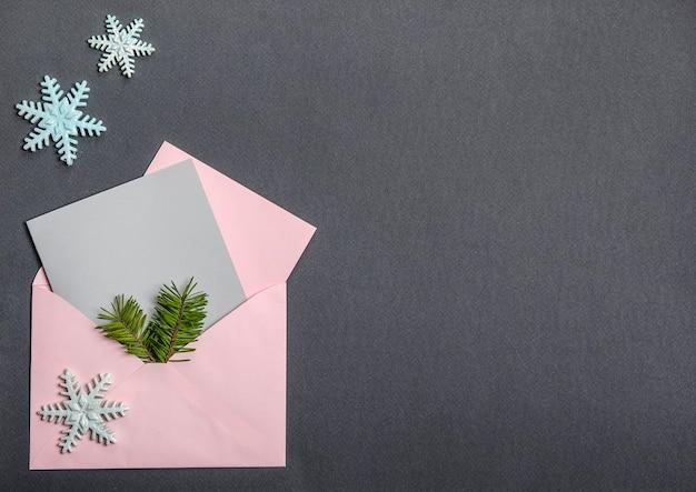Op een zwarte achtergrond, een envelop met ansichtkaarten en een kerstboomtak