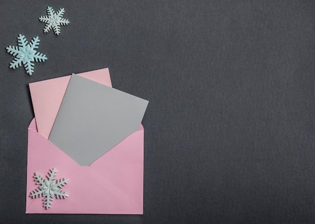 Op een zwarte achtergrond, een envelop met kaarten en sneeuwvlokken. nieuwjaar decoratie.