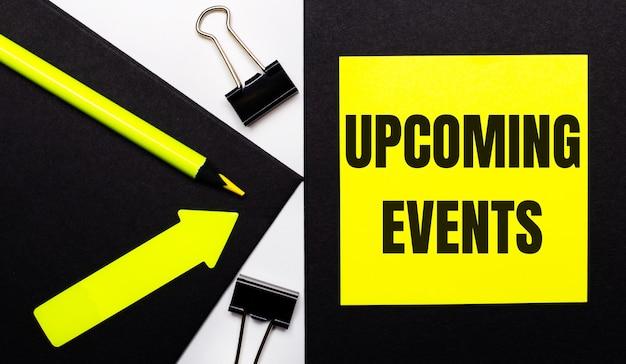 Op een zwarte achtergrond een fel geel potlood en een pijl en een geel vel papier met de tekst upcoming events
