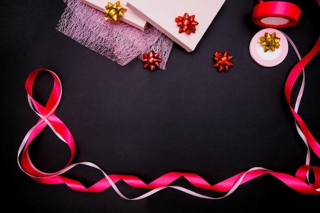 Op een zwarte achtergrond, een roze satijnen lint in de vorm van het cijfer acht. cadeaupapier.