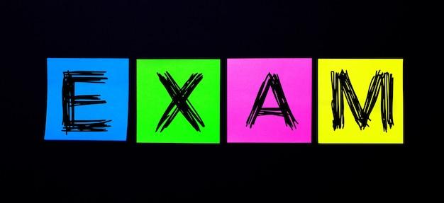 Op een zwarte achtergrond, felgekleurde stickers met het woord exam