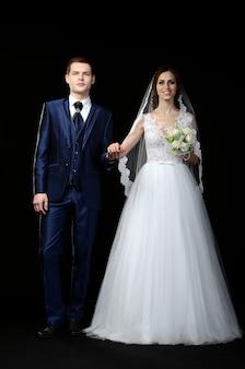 Op een zwarte achtergrond houdt de bruidegom de hand van een bruid, een bruidsboeket een witte jurk