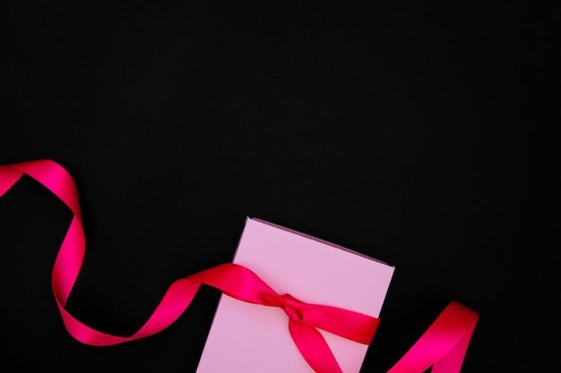 Op een zwarte achtergrond is er een roze geschenkdoos. de doos is vastgebonden met een satijnen lint.