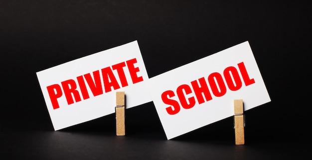 Op een zwarte achtergrond op houten wasknijpers, twee witte blanco kaartjes met de tekst private school