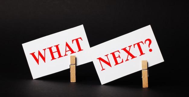 Op een zwarte ondergrond op houten wasknijpers twee witte blanco kaarten met de tekst what next