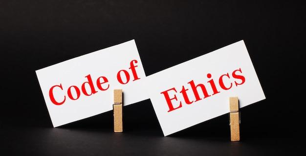 Op een zwarte ondergrond op houten wasknijpers twee witte blanco kaartjes met de tekst code of ethics