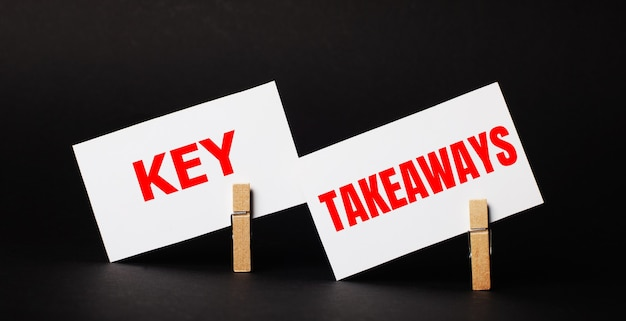 Op een zwarte ondergrond op houten wasknijpers twee witte blanco kaartjes met de tekst key takeaways