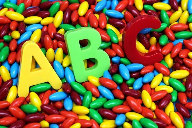 Op gekleurde snoepjes worden gekleurde abc-letters geplaatst. engels voor beginners.