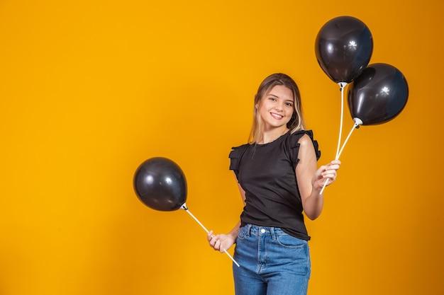 Op gele achtergrond met luchtballonnen studio portret. black friday-uitverkoop